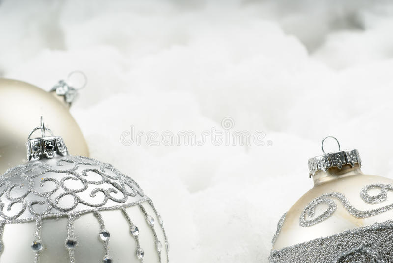 Fragile baubles on cotton. Three New Year's boubles sparkling on white royalty free stock photo