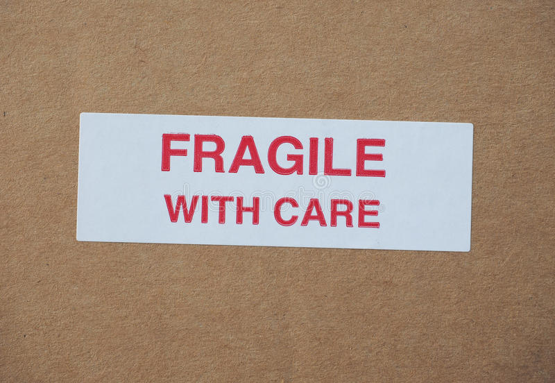 Fragile with care sign. Fragile with care warning sign label tag on a cardboard box packet royalty free stock photos