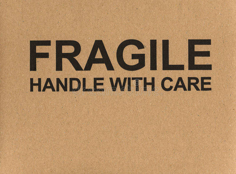 Fragile handle with care label tag. Fragile handle with care warning sign label tag on a cardboard box royalty free stock photo