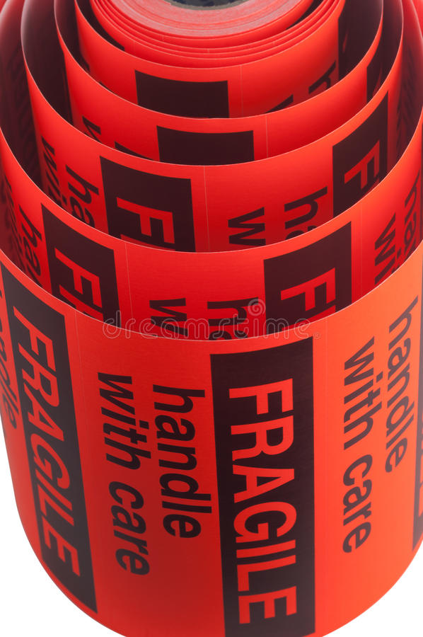 Fragile handle with care labels. A fragile, handle with care roll of tape royalty free stock images