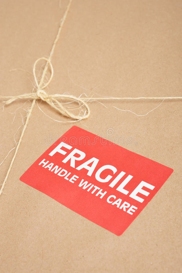 Fragile Package. Wrapped in brown craft paper with label, tag and string on it stock images