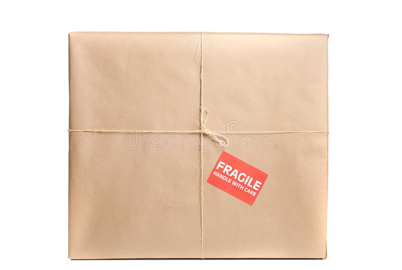 Fragile Package. Wrapped in brown craft paper with label, tag and string on it royalty free stock image