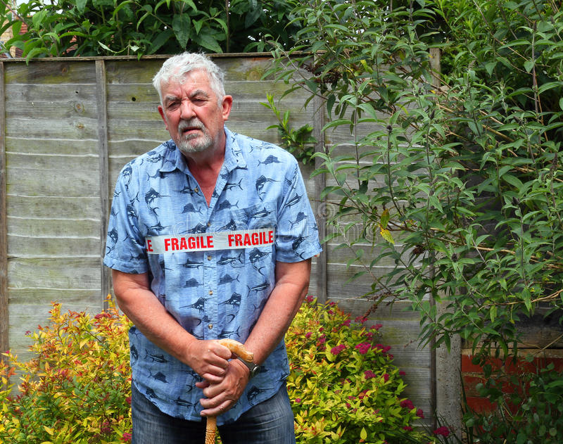 Weak, fragile senior man standing with cane. stock photo