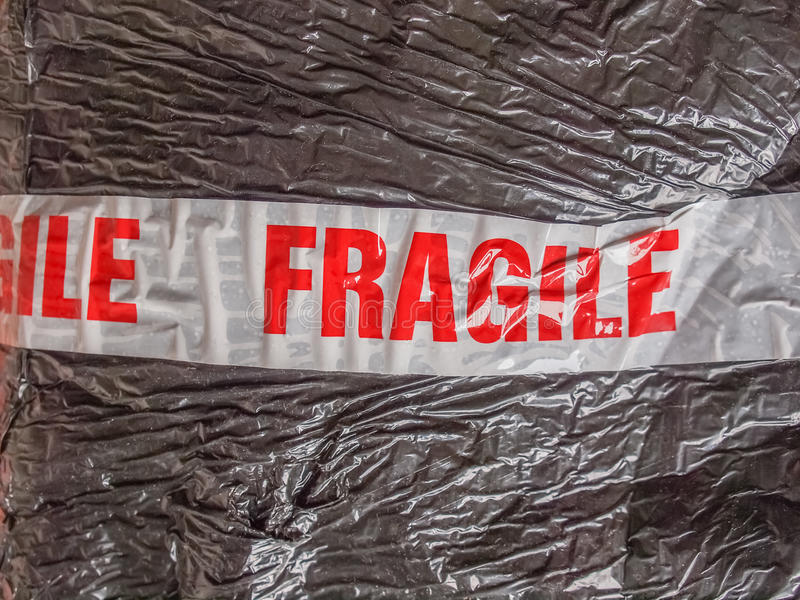 Fragile sign. Fragile warning sign label tag on a packet parcel for mail post shipping stock photos