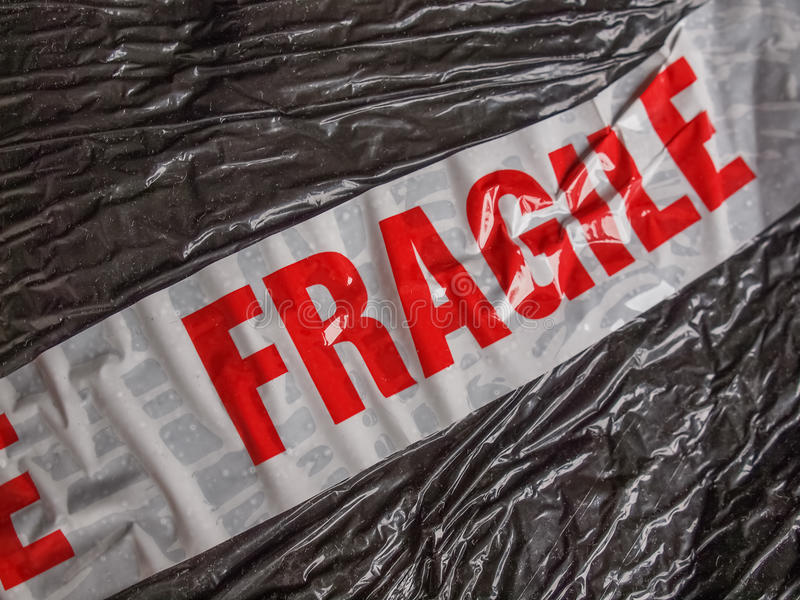 Fragile sign. Fragile warning sign label tag on a packet parcel for shipping stock photography