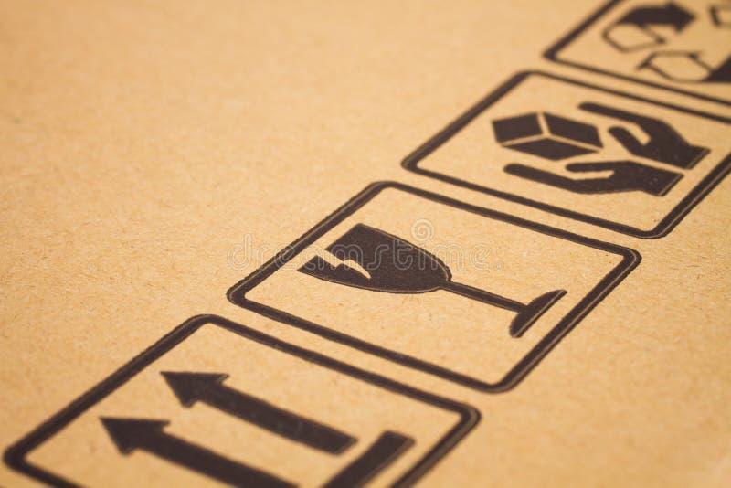 Fragile symbols on cardboard. Image close-up of grunge black fragile symbols on cardboard royalty free stock images