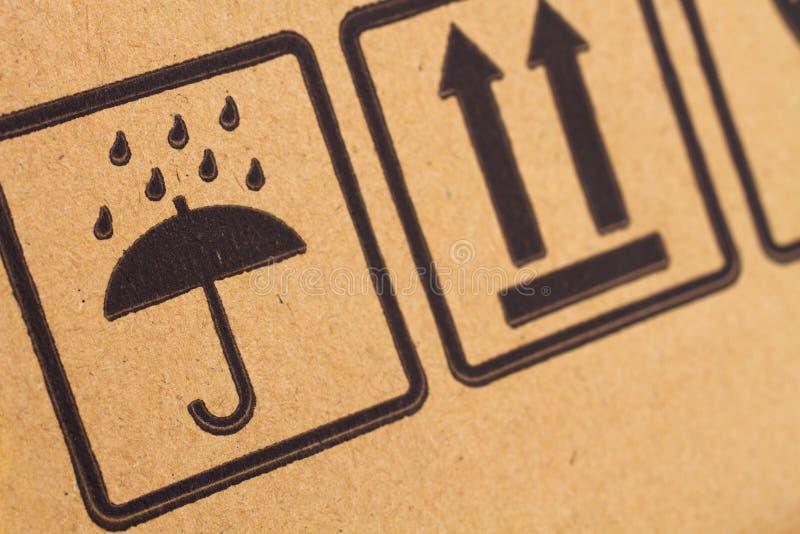 Fragile symbols on cardboard. Image close-up of grunge black fragile symbols on cardboard stock image