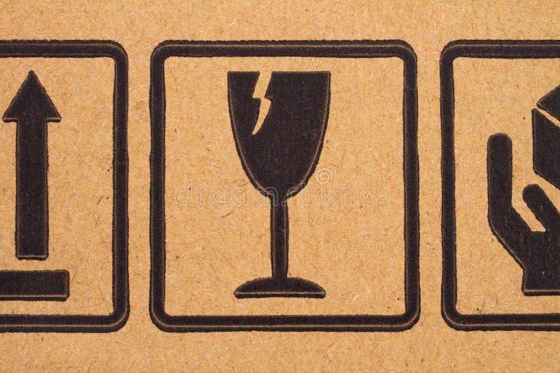 Fragile symbols on cardboard. Image close-up of grunge black fragile symbols on cardboard royalty free stock photography
