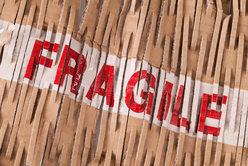 Fragile tape label across packaging. Fragile tape label across cardboard shredded packaging stock photography