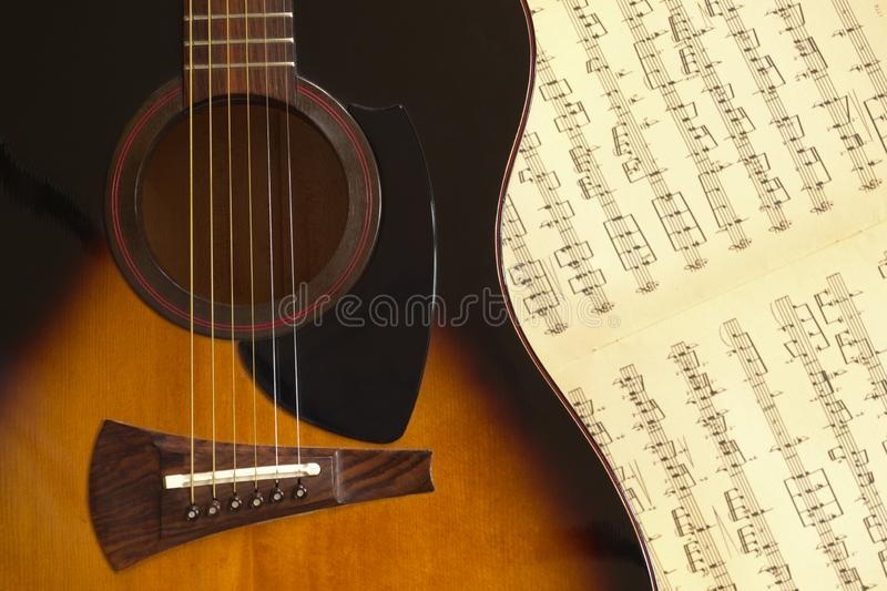 Fragment of an acoustic guitar shown frontally. A fragment of a six-string acoustic guitar on a music album with natural light royalty free stock photography