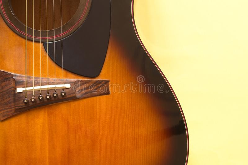 Fragment of an acoustic guitar shown frontally. Fragment of a six-string acoustic guitar on a yellow background with natural light stock images