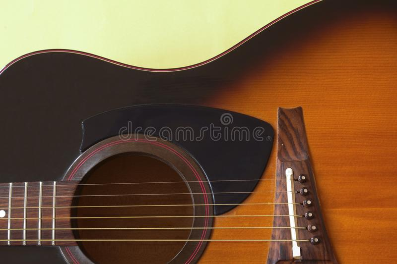 Fragment of an acoustic guitar shown frontally. Fragment of a six-string acoustic guitar on a yellow background with natural light stock photo
