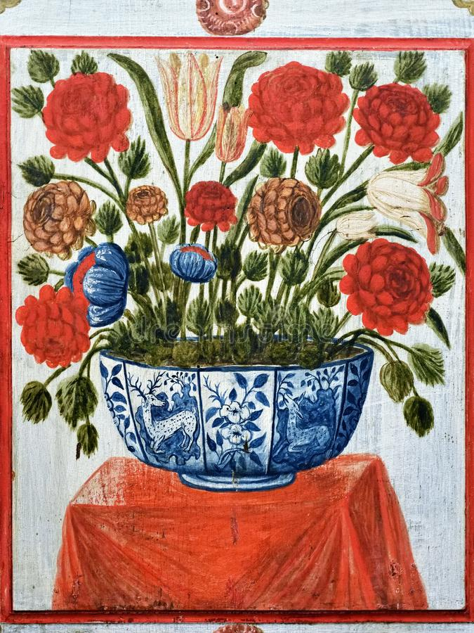 Portuguese medieval art example, Evora, Portugal. Fragment of the ancient plastered wall in Saint Francis church in Evora, Portugal. Red flowers in pot on the stock photos