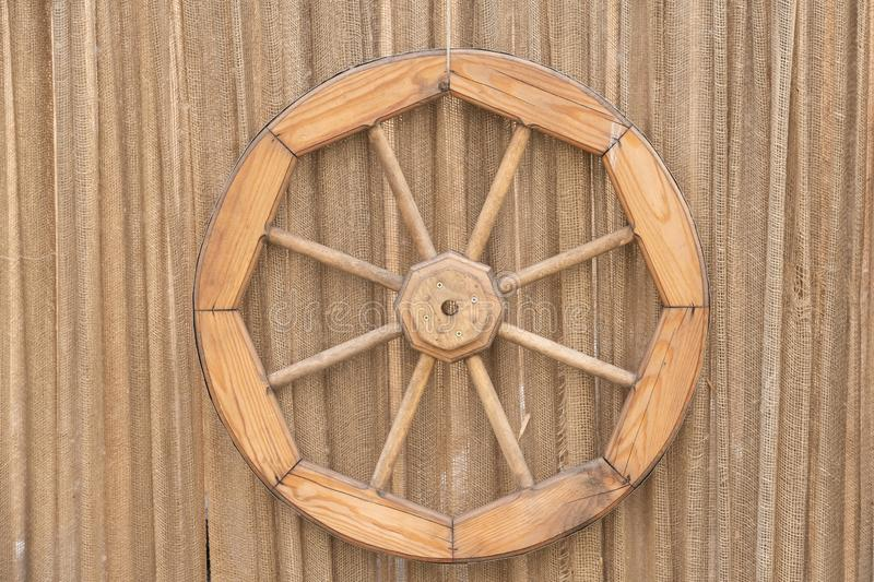 Fragment of an ancient wall with a blue door, an old wooden wheel and a drainpipe royalty free stock photos