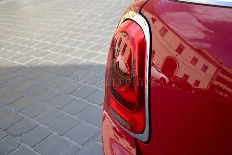 Fragment av den bakre billyktan av den röda bilen på bakgrunden av stenläggningstenar royaltyfri fotografi