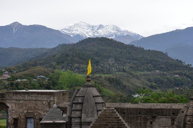 Fragment av den forntida Shiva templet på Baijnath, Himachal Pradesh, Indien med gröna kullar och snöig berg i bakgrunden royaltyfri fotografi