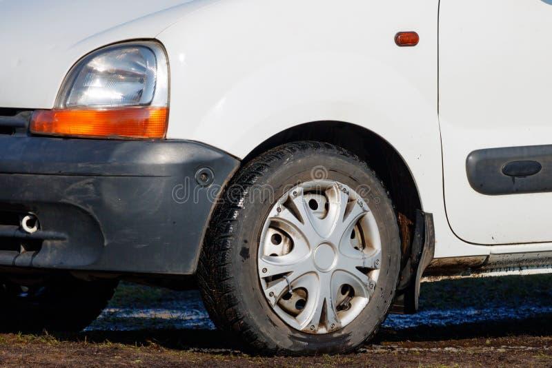 Fragment av den gamla bilen med skadat billyktaanseende i gyttjanärbilden royaltyfri fotografi