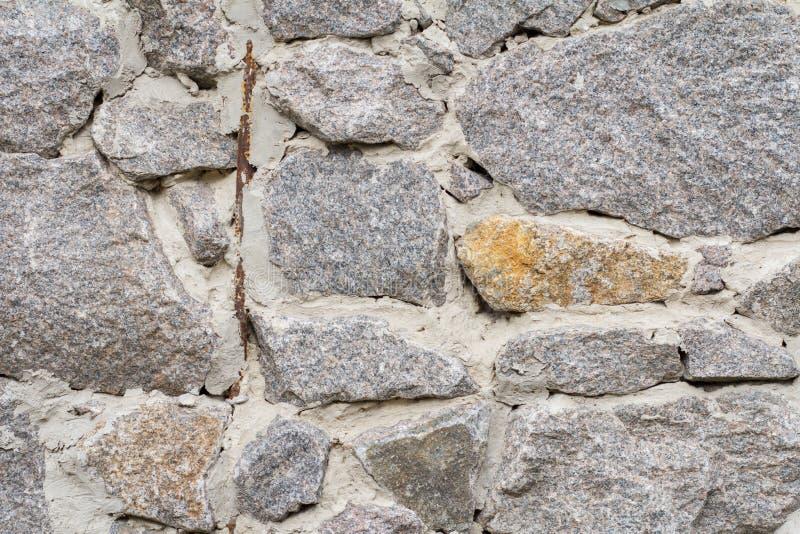 Fragment av den gråa stenväggen med cementlösningen Bekläda beskådar royaltyfri fotografi