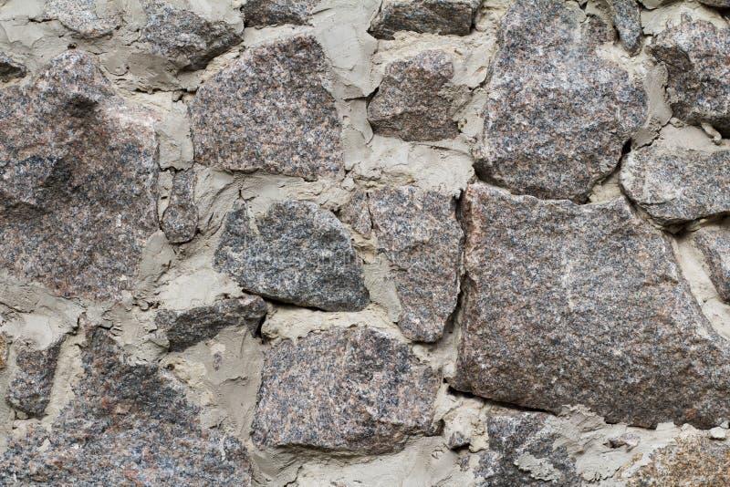 Fragment av den gr?a stenv?ggen med cementl?sningen Bekl?da besk?dar arkivfoto