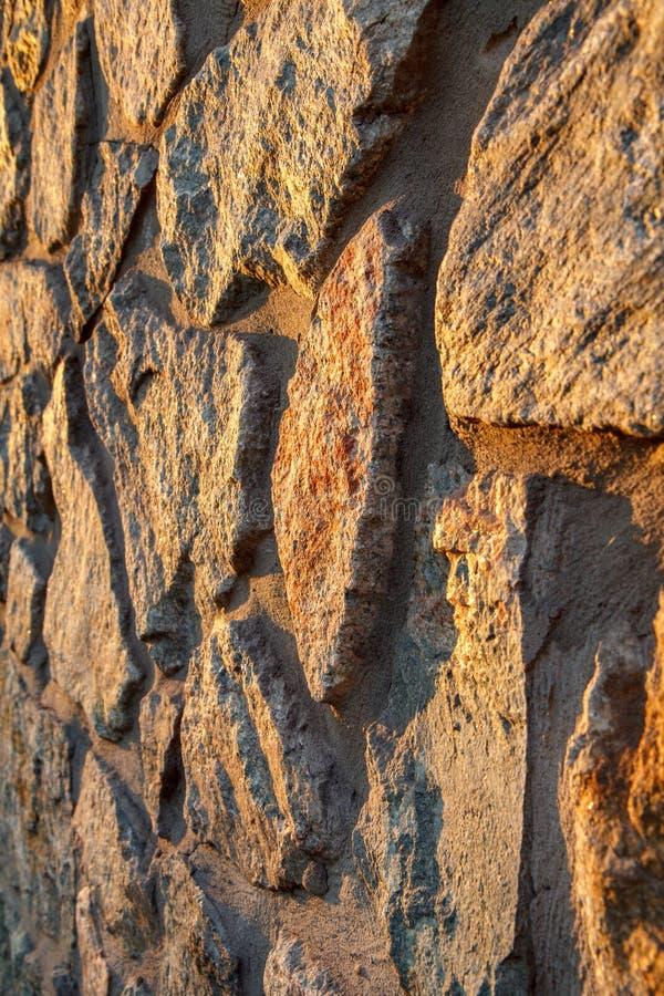 Fragment av den solbelysta stenväggen Slapp fokus arkivfoto
