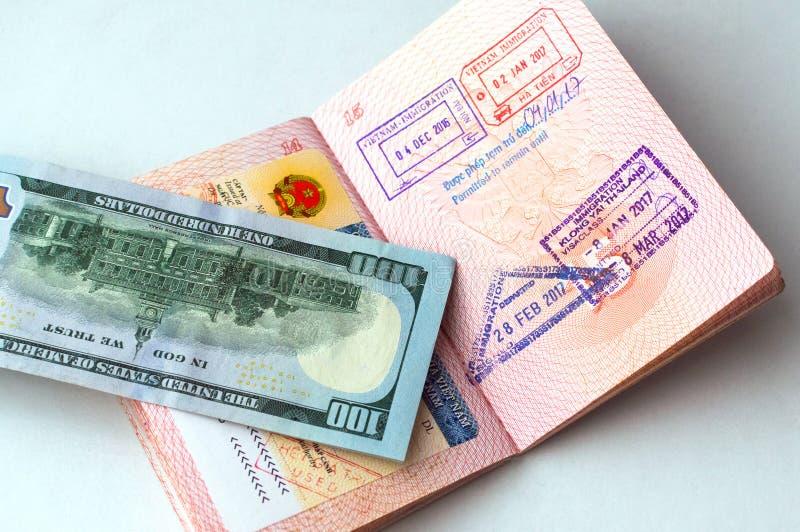 Fragment av den vietnamesiska visumklistermärken i ett pass, invandringstämplar i passet, sedel för 100 USD arkivfoton