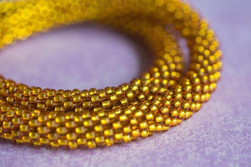 Fragment av en briljant gul halsband från pärlor fotografering för bildbyråer