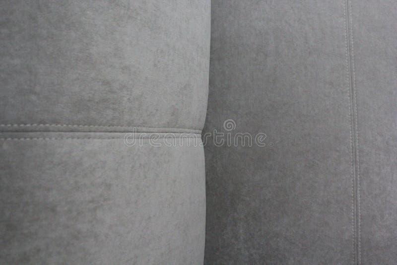 Fragment av en grå veloursoffa arkivfoto