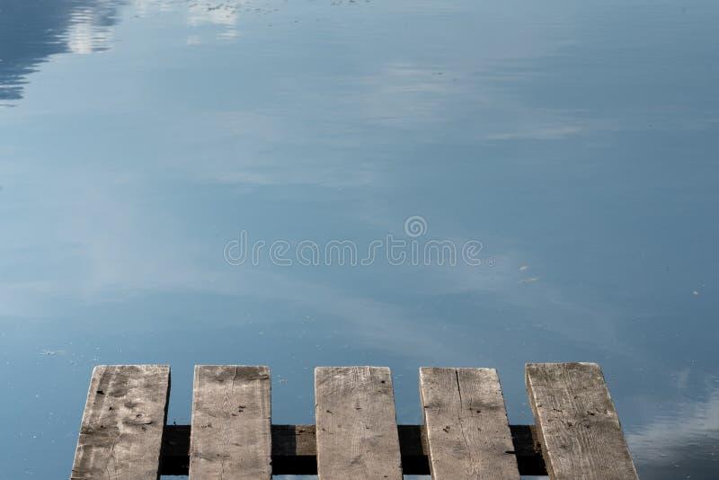 Fragment av en liten träbrygga på bakgrunden av sjön Reflexion av himlen i sj?n royaltyfria foton