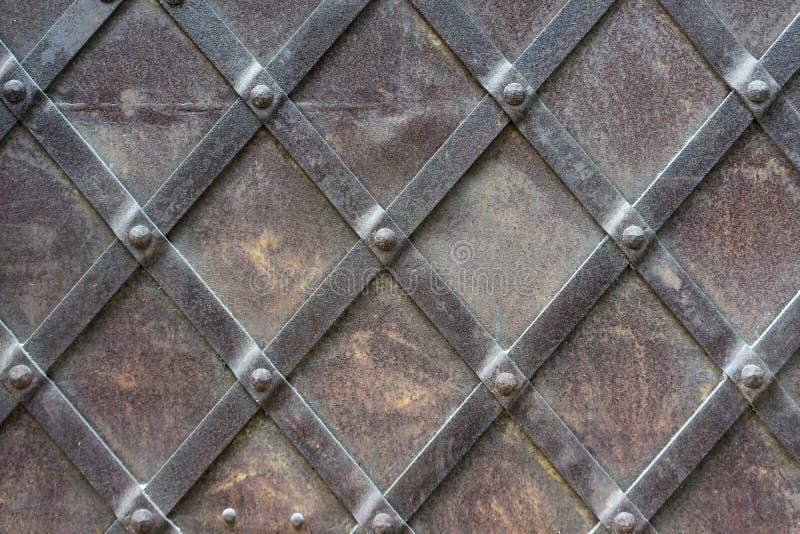 Fragment av en metalldörr med nitar fotografering för bildbyråer