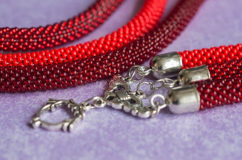 Fragment av en prydd med pärlor halsband av röd färg arkivbilder