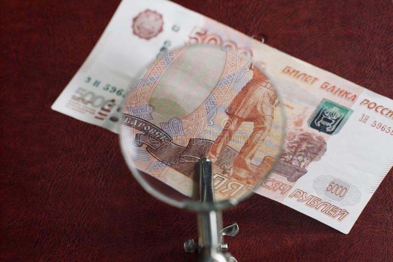 Fragment av en räkning av 5 000 ryska rubel under ett förstoringsglas royaltyfria foton