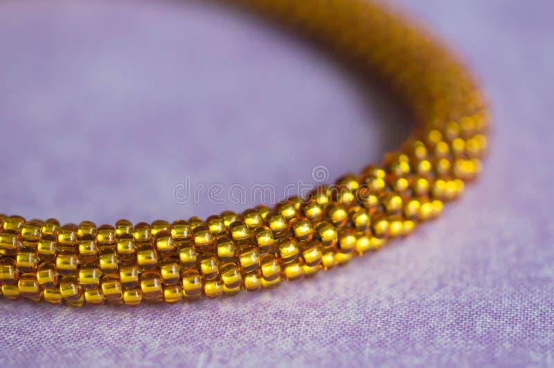 Fragment av en stucken gul halsband från pärlor arkivbild