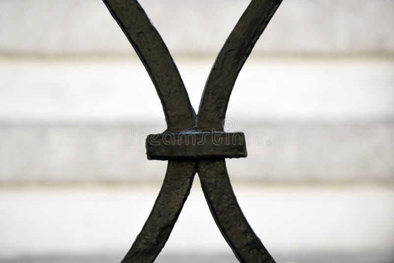 Fragment av ett gammalt smidesjärnstaket, i form av bokstaven X arkivfoton