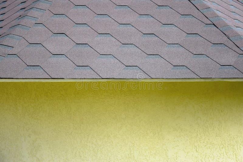 fragment av ett gult litet hus med ett tak som täckas med böjliga singlar i form av honungskakor arkivbilder