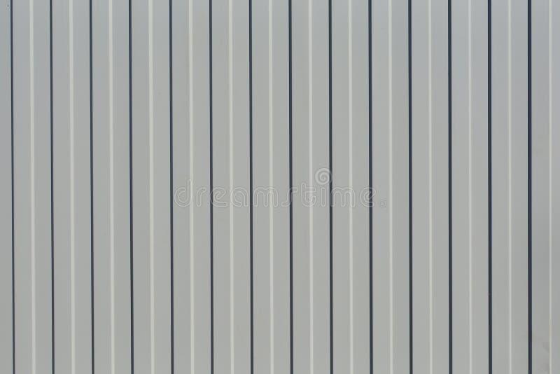 Fragment av ett staket från det profilerade arket av grå färger Abstrakt begrepp geometrisk bakgrund royaltyfri illustrationer