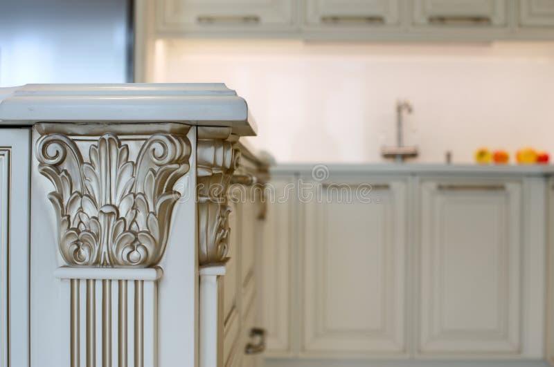 Fragment av ett stilfullt köksbord i en flott stil med ett kök i bakgrunden royaltyfri foto