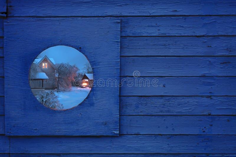 Fragment av ett trästaket med ett runt fönster I fönstret är en härlig vinternattsikt av byhuset arkivbilder