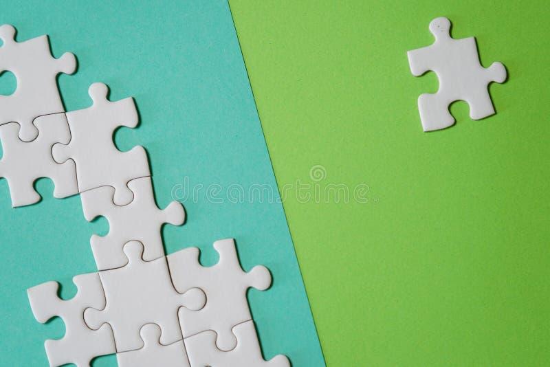 Fragment av ett vikt vitt pussel och en h?g av uncombed pusselbest?ndsdelar mot bakgrunden av en kul?r yttersida vektor illustrationer