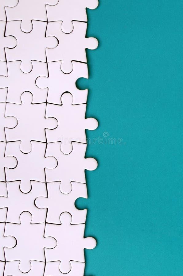 Fragment av ett vikt vitt pussel på bakgrunden av en blå plast- yttersida Texturfoto med kopieringsutrymme för text arkivfoton
