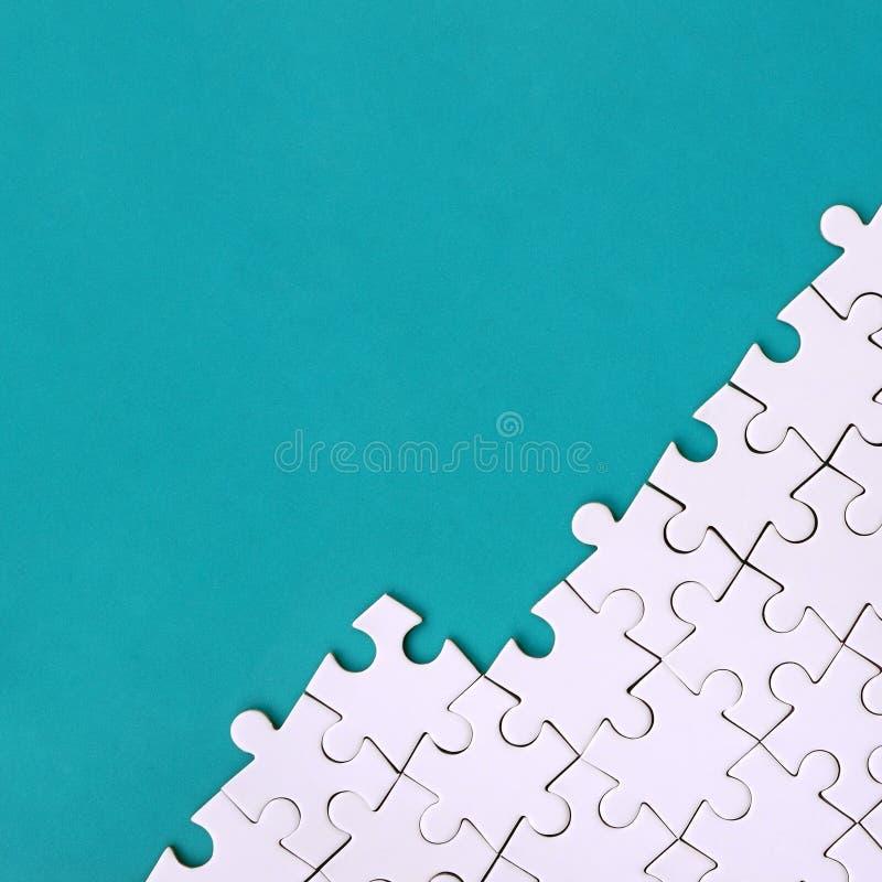 Fragment av ett vikt vitt pussel på bakgrunden av en blå plast- yttersida Texturfoto med kopieringsutrymme för text arkivbild
