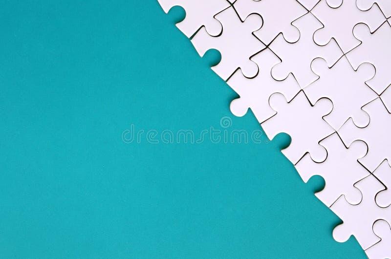 Fragment av ett vikt vitt pussel på bakgrunden av en blå plast- yttersida Texturfoto med kopieringsutrymme för text royaltyfria bilder