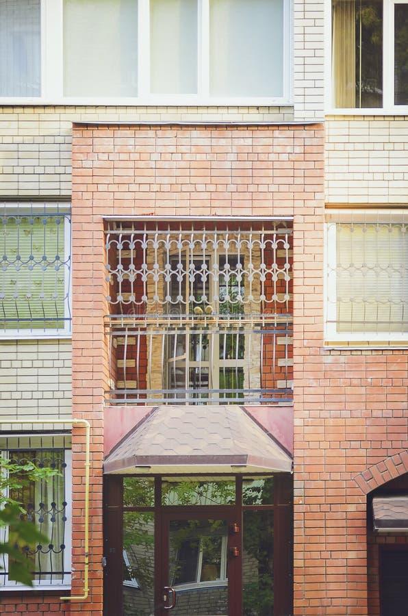 Fragment av ettvåning tegelstenhus som göras av röd tegelsten med stänger royaltyfri fotografi
