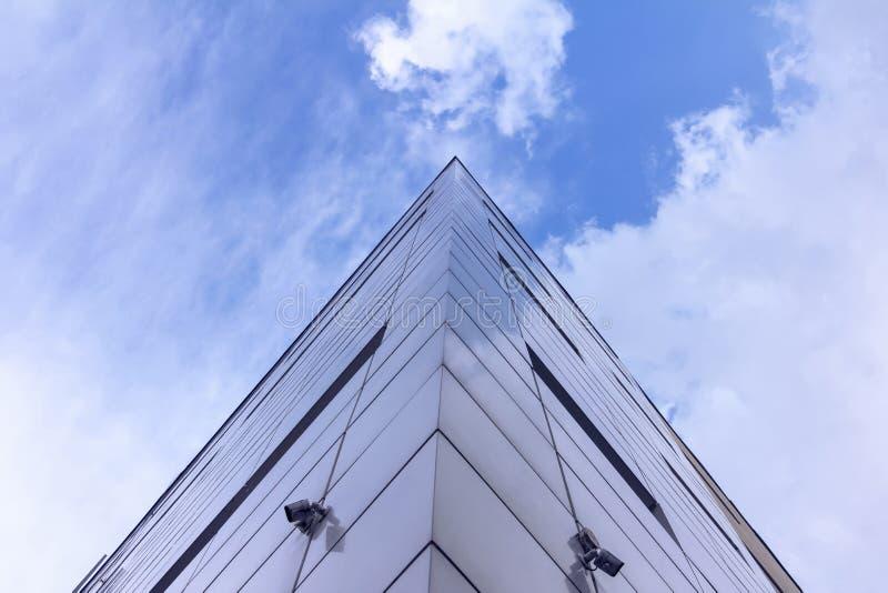 Fragment av fasaden av abstrakt modern kommersiell arkitektur, hörnet av väggarna under en blå molnig himmel arkivfoton