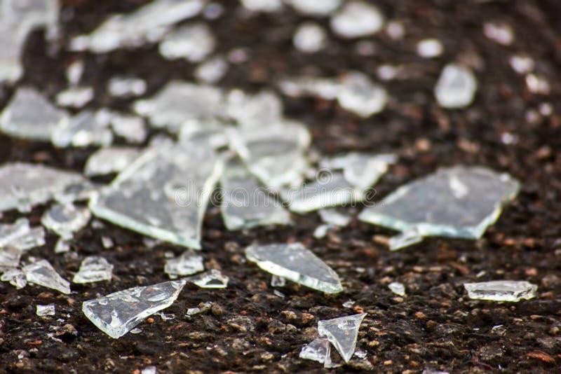 Fragment av genomskinligt exponeringsglas på asfalt arkivfoton