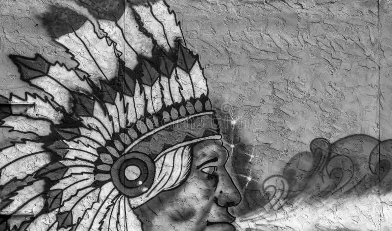 Fragment av grafitti av en indisk chef på en betongväggbakgrund royaltyfri foto