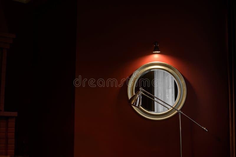 Fragment av inre i ett mörkt sätt: en rund spegel i en massiv ram och en golvlampa royaltyfri foto