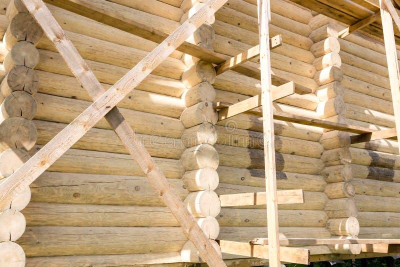 Fragment av konstruktionen av ett trähus som göras av runda journaler Nära övre bild av journalhuset royaltyfri foto