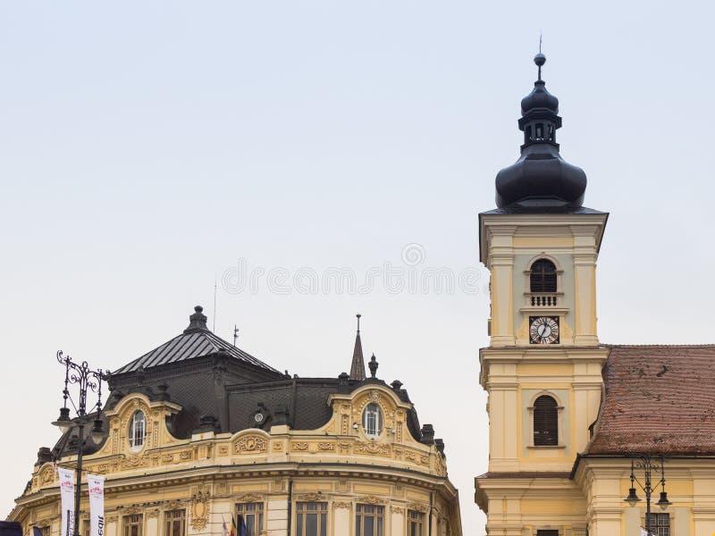 Fragment av Roman Catholic Church av den heliga Treenighet och det Sibiu stadshuset på den stora fyrkanten i den Sibiu staden i R royaltyfria bilder