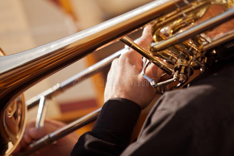 Fragment av trombonen i händerna av musikern arkivfoto