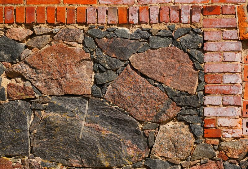 Fragment av väggen av stenar för röd tegelsten och grå färg Tegelsten- och stenbakgrund grå red arkivbild